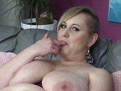 Толстая баба с массивными дынями трахает себя пальцами