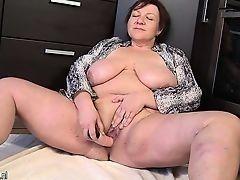 Толстая большегрудая пожилая женщина рукоблудствует и вставляет в влагалище розовую дилдо игрушку